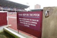 "A set of claret painted hardwood and metal low double gates with ""Please Keep Off The Grass Sign"", used pitch side of the Betway Stand."