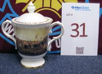 "A Royal Doulton bone china two-handled cup and lid. Cup transfer printed with decoration of the famous painting by Thomas Hemy of Sunderland v Aston Villa in 1895 and Football League crest to the reverse. Cover transfer printed inscription ""To commemorate the 100th championship season of the Football League 1888-1988"", all on a white glazed ground with gilt detailing."