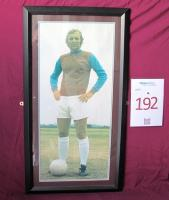 A framed picture of Bobby Moore in a West Ham United kit. Originally sited in the Greenwood and Lyall Lounge reception staircase. The most famous Hammer of them all, and the finest defender in the world at the peak of his career. A blond colossus at the heart of West Ham's defence for over a decade, he represented his country at every level and played 647 League and Cup games for his club. Making his League debut against Manchester United on the 8th September 1958 in a 3-2 victory, he was a surp