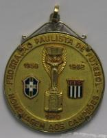 A gilt-metal and enamel medallion, the obverse cast with the Jules Rimet trophy and dated 1958, 1962 and 1970, the border inscribed Federacao Pauliste de Futebol, Homenagem AOS Campeos, the reverse inscribed Conquista da Taca Jules Rimet. The commemorative medal was given to Bobby Moore by the Federacao Paulista de Futbol (Sao Paulo).