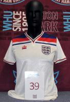 A white, red and blue England short-sleeved International shirt, with V-neck collar and embroidered Three Lions cloth badge, worn by Trevor Brooking.