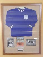 A framed match exchanged Greece shirt, England 3 Greece 0, UEFA European Championship Group 3 Qualifying, Wembley Stadium, 21st April 1971, Georgius Koudas wore the No.7 shirt which he exchanged with Martin Peters. England winning 3-0 with goals from Martin Chivers, Geoff Hurst and Francis Lee. Originally displayed in the Betway stand main central staircase.